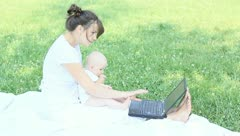 Young mother work at the computer with a baby in her arms Stock Footage