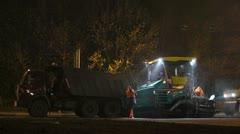 Truck unload asphalt to paver machine - stock footage
