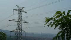 High-voltage wire tower in urban city,wind tree,distant mountain & hill. Stock Footage