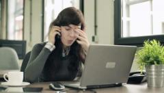 Angry businesswoman with cellphone and laptop and documents in the office HD Stock Footage