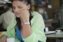 Sad woman drinking coffee in restaurant, outdoors, steadycam shot Stock Footage