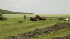 The tractor loads hay aboard Stock Footage