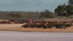 Young man hiking in desert towards camera aroaround Pink salt lake Australia Stock Footage