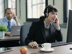 Friendly happy female helpdesk consultant in the office NTSC - stock footage