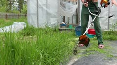 Man with weed trimmer working on courtyard Stock Footage