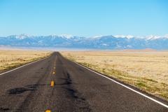 Empty freeway approaching mountains range Stock Photos