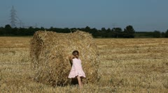 Child Pushing a Bale of Straw, Little Girl Playing with a  Ballot of Straw Stock Footage