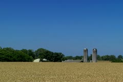 Driving by a farm grain field with silos in background Stock Footage