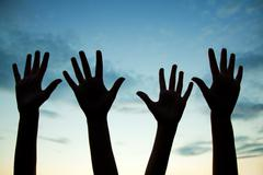 Four raised hands Stock Photos