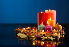 a lot of burning colorful candles against dark blue background - stock photo