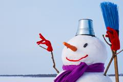 lonely snowman at a snowy field - stock photo