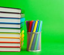 Stack of colorful books and socket with felt pens Stock Photos