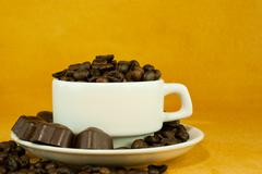 cup full with coffee beans and chocolate candies - stock photo