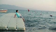 Young boy sitting on platform floating on the water HD Stock Footage
