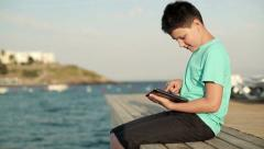 Happy boy playing with tablet computer on wooden pier by the sea HD Stock Footage