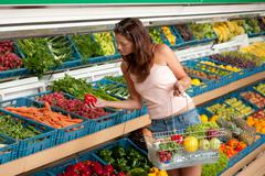 Grocery store shopping - young woman buying vegetable Stock Photos