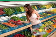 Stock Photo of grocery store shopping - young woman buying vegetable