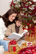 young mother with son reading book on christmas - stock photo