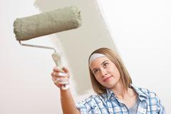 Home improvement: young woman with paint roller Stock Photos