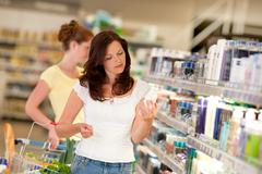 Shopping series - brown hair woman in cosmetics department Stock Photos
