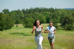 young couple jogging outdoors in spring nature - stock photo