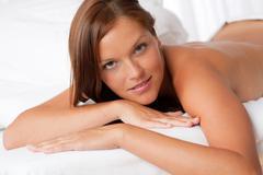 white lounge - naked woman lying on white bed - stock photo