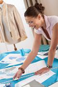 professional tailor working with fashion sketches - stock photo