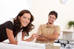 Stock Photo of smiling man and woman with architectural model