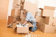 Stock Photo of moving house: happy woman unpacking box