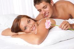Stock Photo of happy man and woman lying down in bed together