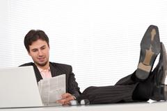 successful modern businessman with laptop and newspaper - stock photo