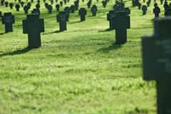 row of crosses in cemetery with grass - stock photo