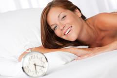 white lounge - smiling woman with alarm clock - stock photo