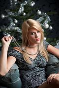 provocative woman posing in front of christmas tree - stock photo