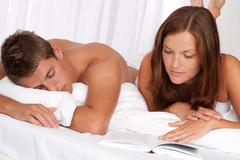 Stock Photo of young man and woman lying down together on white sofa