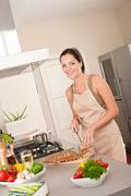 Stock Photo of woman cutting bread in the kitchen