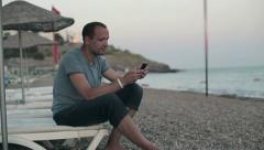 Young man using smartphone on the beach HD Stock Footage