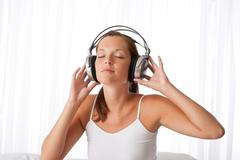 Stock Photo of young woman in white with headphones