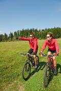 young couple riding mountain bike in spring meadow - stock photo