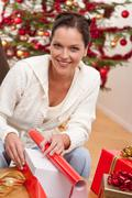 Young woman packing christmas present Stock Photos