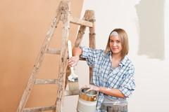 Stock Photo of home improvement: smiling woman with paint and brush painting wall