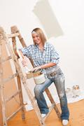 Home improvement: smiling woman with paint Stock Photos