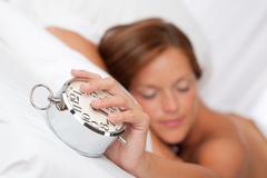 White lounge - beautiful sleeping woman holding alarm clock Stock Photos