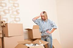 Moving house: young woman unpacking box Stock Photos