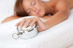 white lounge - woman holding silver alarm clock - stock photo