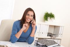 Stock Photo of smiling female architect holding phone and pen