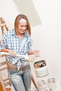 home improvement: smiling woman with paint and brush painting wall - stock photo