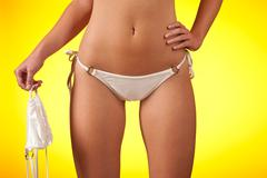 part of female body wearing white bikini   holding bra - stock photo