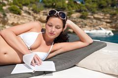 attractive woman sunbathing on luxury boat - stock photo