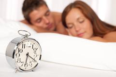 young couple lying in white bed with alarm clock - stock photo